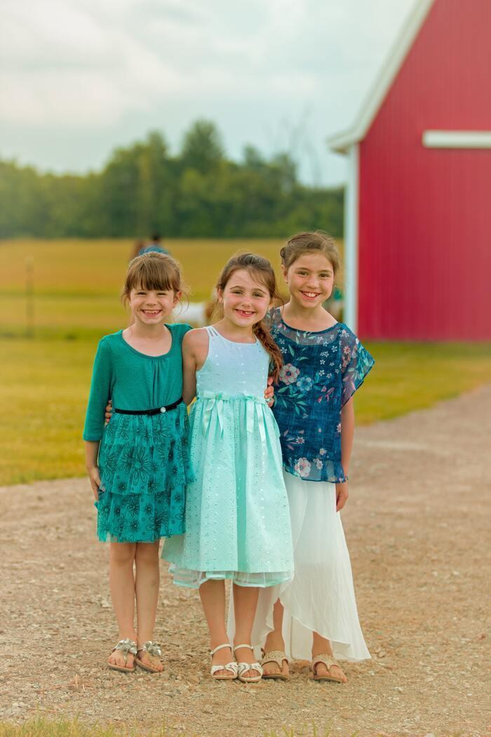 Dziewczynki ubrane w odświętne sukienki pozują do zdjęcia