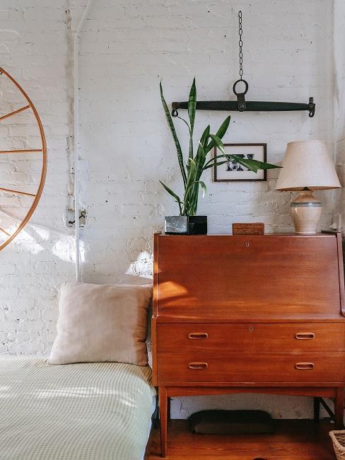 Sypialnia z drewnianą komodą, lampką oraz roślinami - dom rustykalny