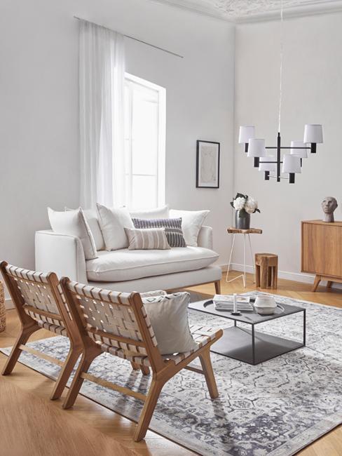 Dom rustykalny: jasny salon z białą kanapą oraz krzesłami z naturalnych materiałów z dywan i stolikiem kawowym