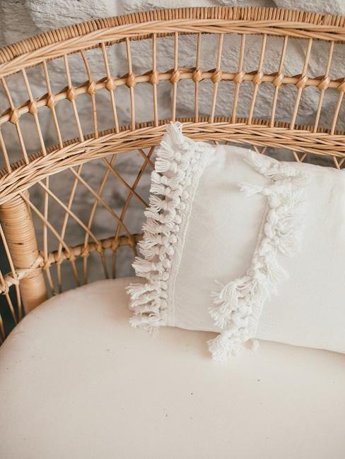 Krzesło z wikliny i biała poduszka boho