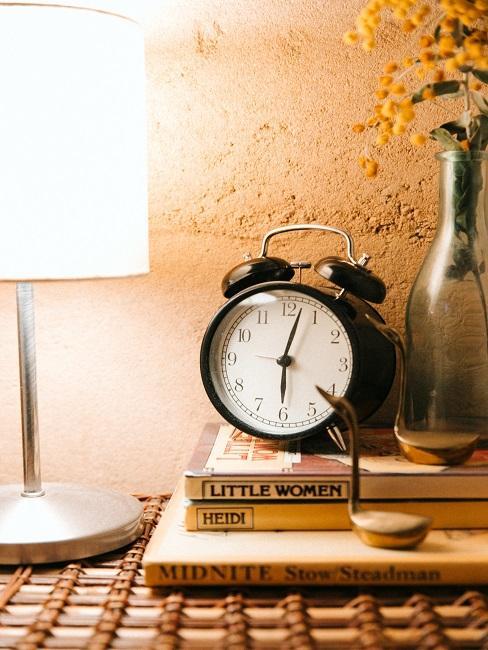Dom rustykalny: lampa nocna na stoliku z zegarkiem i małym wazonem
