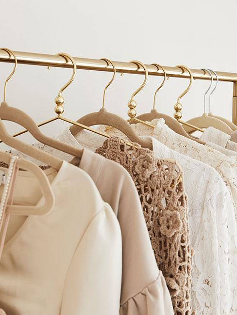 Ubrania zawieszone na złotym drążku