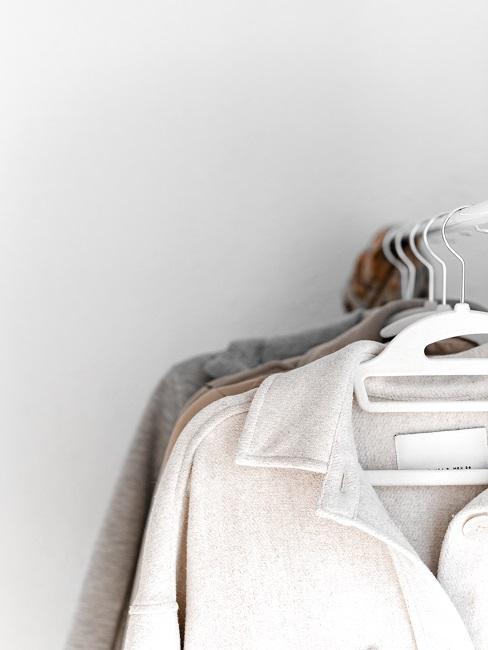 Ubrania na drążku na białym tle