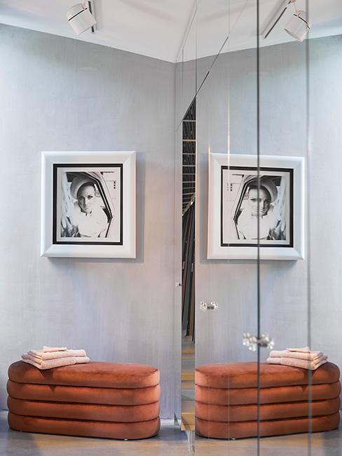 Nowoczesny lustrzana garderoba z małą ławka z aksmaitu w kolorze terakoty i czarnobiałym dzjęciem na ścianie