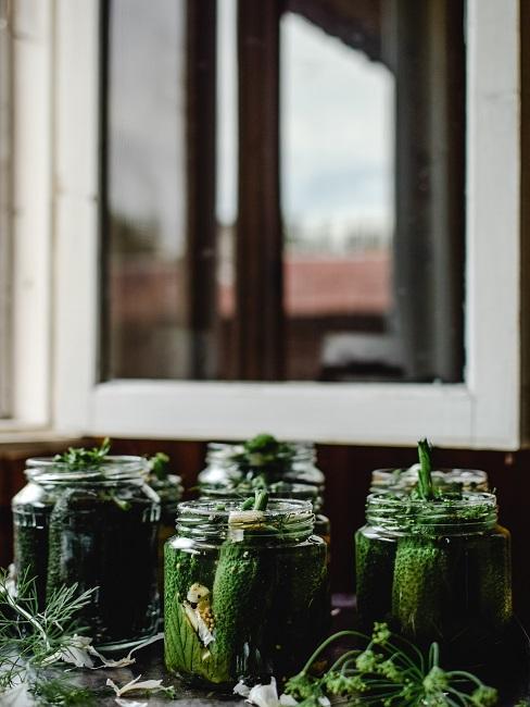 Kilka słoików na stole z ogórkami, zgodnie z przepisem jak zrobić ogórki kiszone