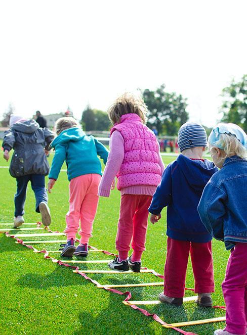 Dzieci bawiące się na zewnątrz w ubraniach sportowych z wyprawki do przedszkola