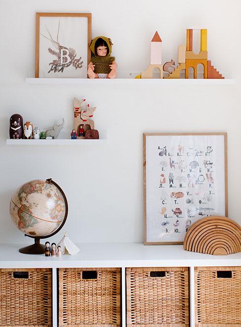 Poukładane zabawki na półkach i globus na stole w przedszkolu