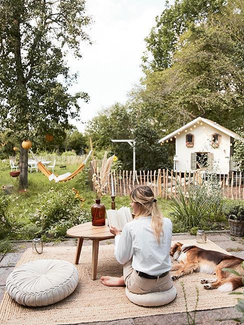 kobieta na ganku z psem w rustykalnym domem