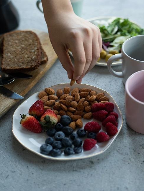 Owoce i orzechy na talerzu, idealne w trakcie postu przerywanego