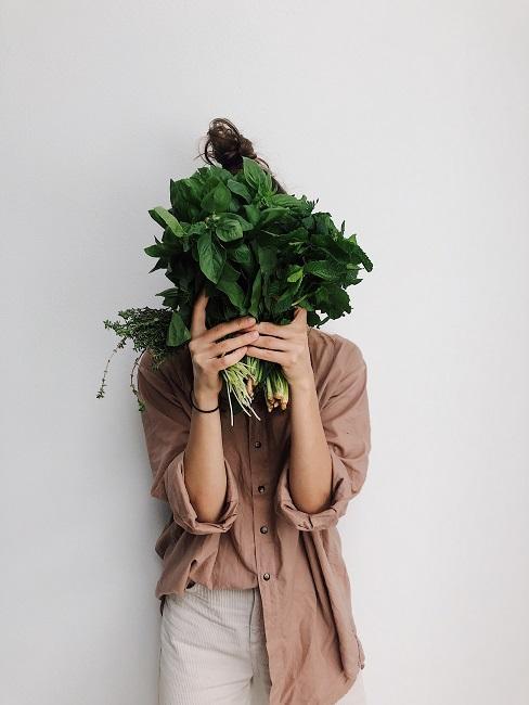 Kobieta ubrana beżową koszule zasłania swoją twarz szpinakiem