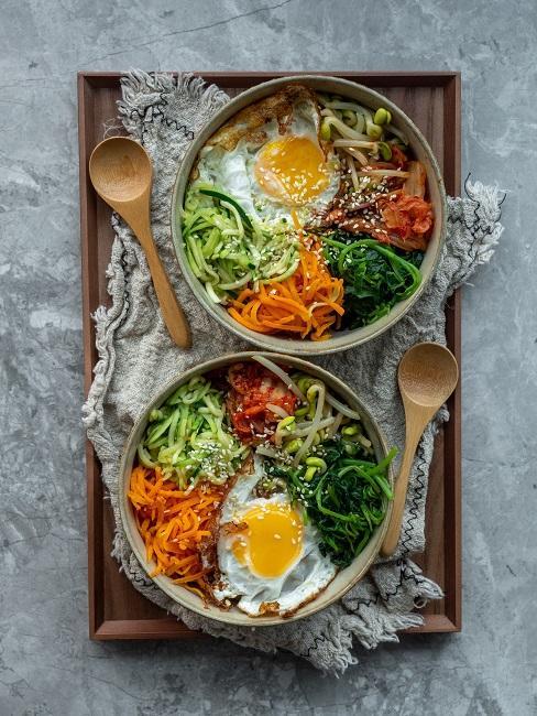 Na desce miski pełne warzyw i z jajkiem