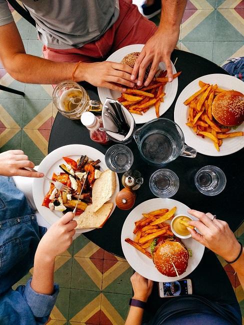 Grupa znajomych siedząca w restauracji i jedząca fast food