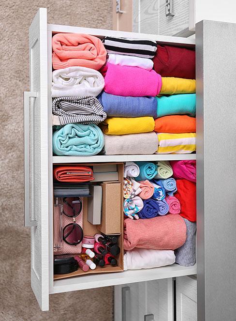 kolorowe bluzki i akcesoria w pojemnikach w szufladzie
