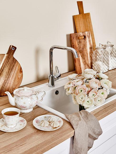 Blat drewniany z kwiatami, deskami do krojenia i filiżanką do herbaty
