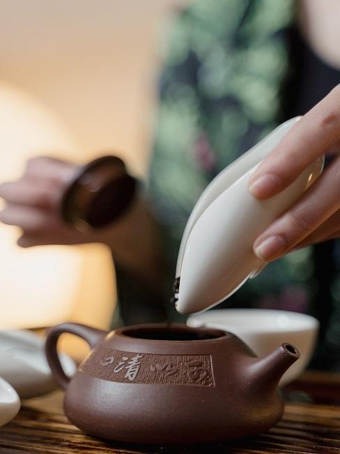 Proces parzenia herbaty, gdzie kobieta wsypuje herbatę do brązowego czajnika