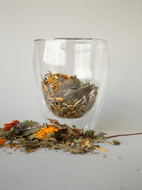 Liście herbaty wsypane do przezroczystego kubka