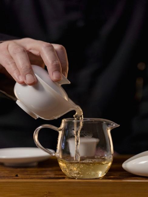 Proces parzenia herbaty, nalewanie naparu do dzbanka