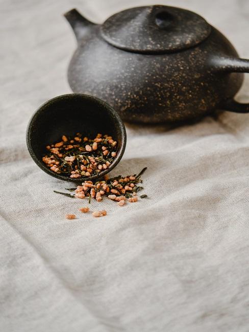 Ciemny czajnik z herbatą na obrusie