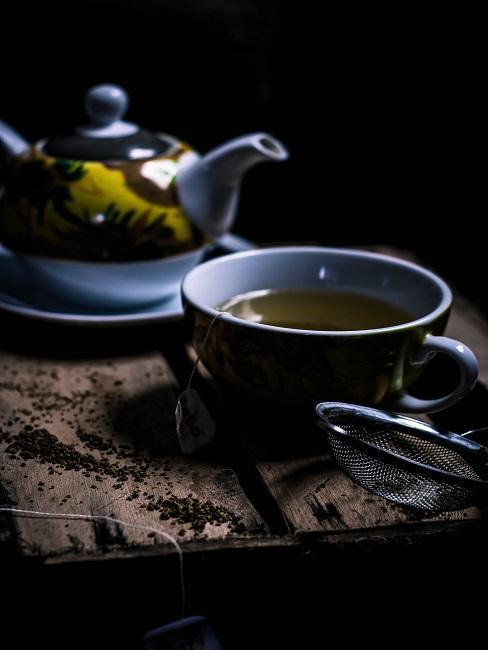 Herbata w niebieskiej filiżance obok czajnika