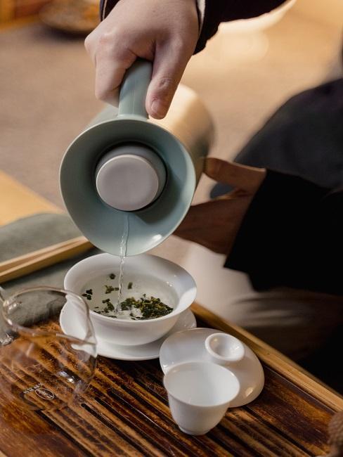 Proces parzenia herbaty, nalewanie naparu do filiżanki