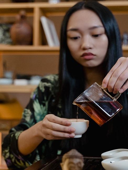 Kobieta w trakcie nalewania herbaty