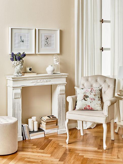 biała atrapa kominka obok pikowanego fotela w salonie w stylu prowansalskim