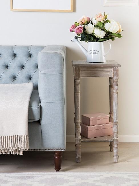 zbiżenie na błękitną pikowaną sofę obok stolika pomocniczego z kwiatami w stylu prowansalskim