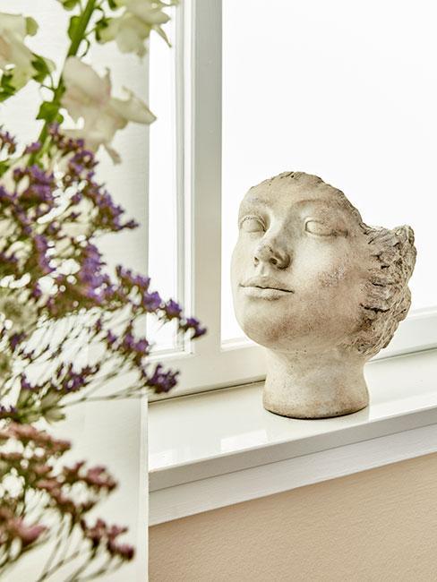 zbliżenie na doniczkę rzeźbę antyczną na parapecie w salonie w stylu prowansalskim