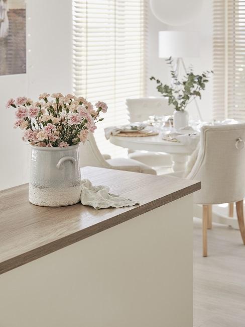 widok z białej wyspy kuchennej z wazonem z goździkami na jasną jadalnię w stylu prowansalskim