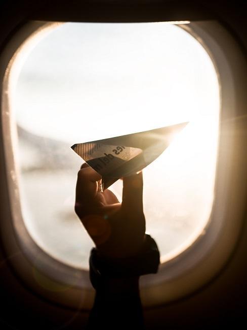 Samolot z papieru na tle okna w samolocie