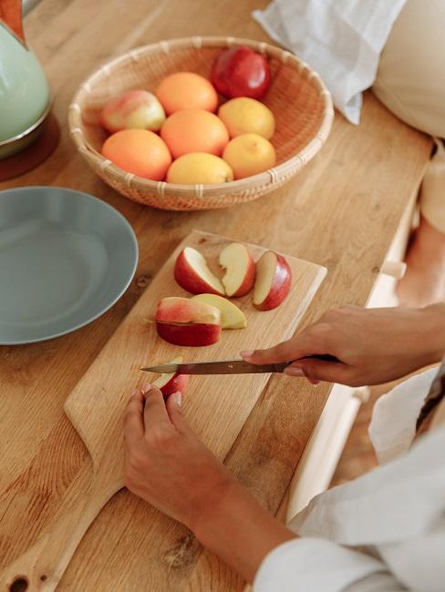 Deska do krojenia z pokrojonymi w ćwiartki jabłkami