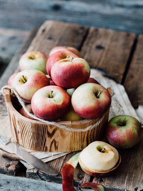 Wiadro pełne jabłek stojące na deskach
