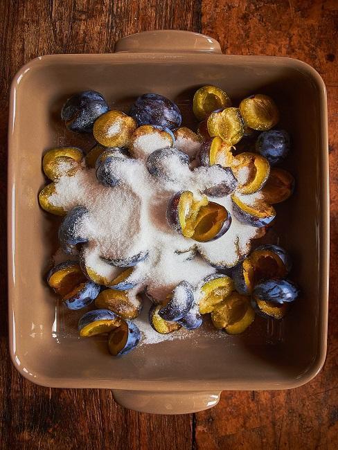 Śliwki posypane cukrem, przygotowywane do słoików, aby zapasteryzować
