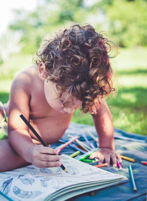 Małe dziecko rysujące na kocu w ogrodzie