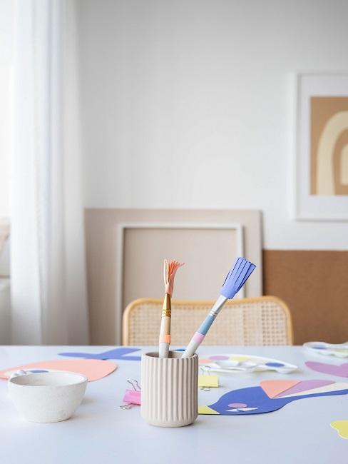 Pędzle w farbie oraz prace plastyczne na stole