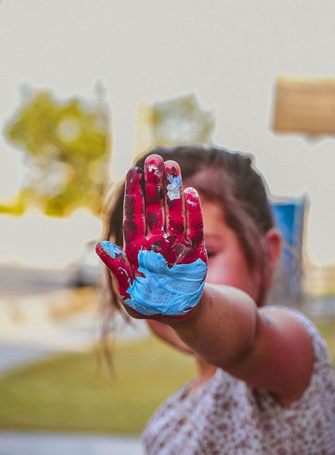 Dziewczynka z pomalowaną farbami dłonią