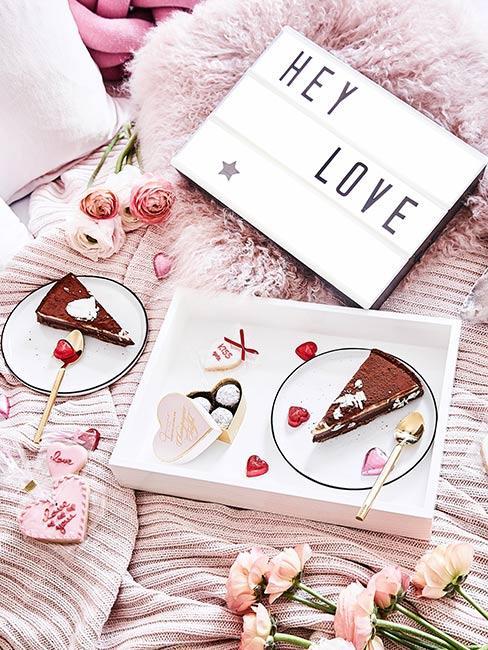 ciasto do łóżka na różowej narzucie z neonowym napisem