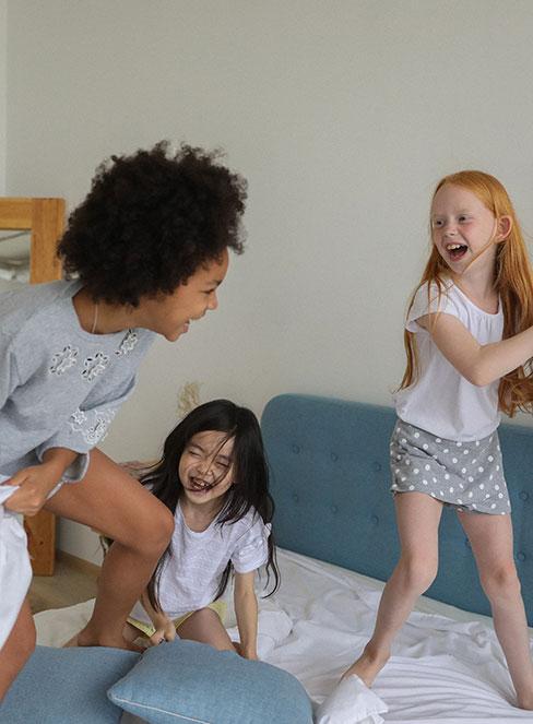 dziewczynki bawiące się w łóżku podczas piżama party