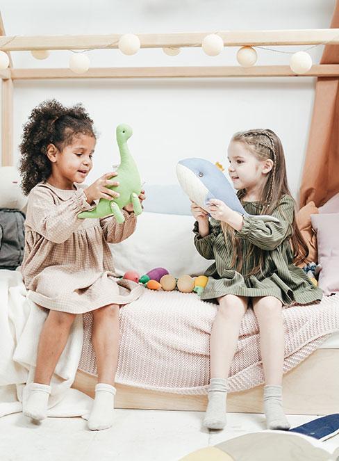 dwi dziewczynki bawiące się zabawkami podczas piżama party