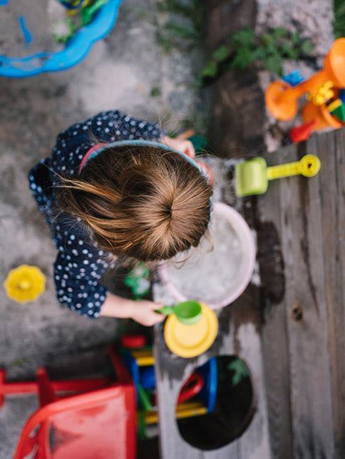 dziewczynka bawiąca się foremkami w piasku
