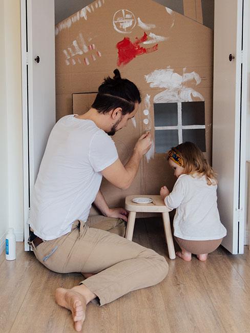 tata z córką malujących na tekturowym domku