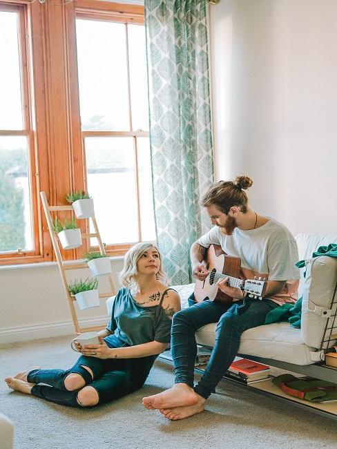 Chłopak siedzi na sofie i gra na gitarze obok dziewczyny siedzącej na podłodze