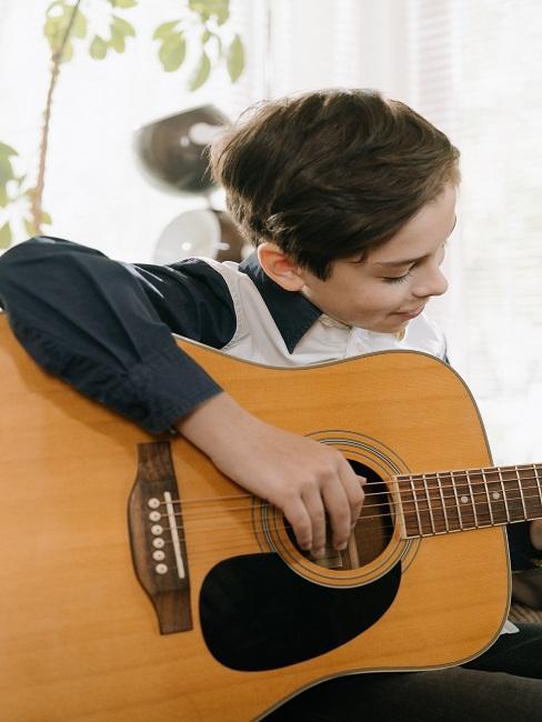 Chłopak gra na gitarze akustycznej