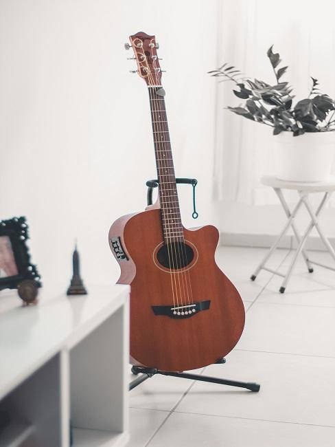 Gitara na stojaku w jasnym salonie