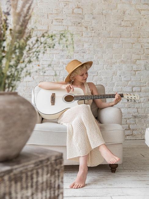 Kobieta gra na gitarze w jasnym salonie