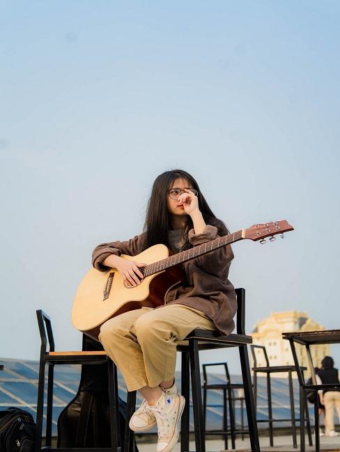 Dziewczyna gra na gitarze na świeżym powietrzu