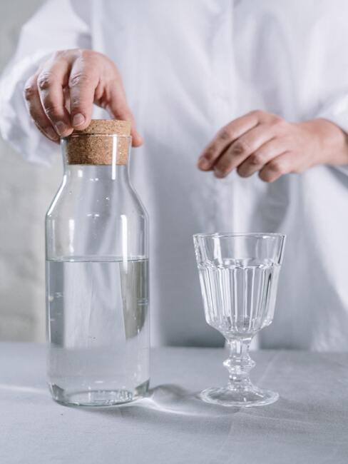 Kobieta nalewająca wodę z karafki