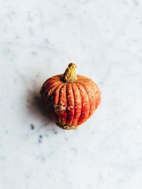 Pomarańczowa dynia leżąca na stole
