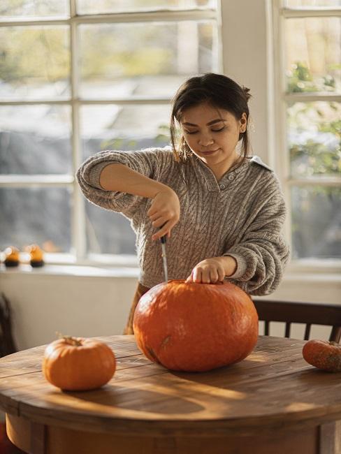 Kobieta przekrajająca dynie na przetwory z dyni