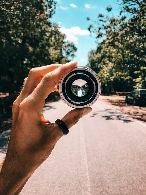 Osoba trzyma soczewkę do aparatu fotograficznego